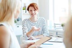 Optimistischer kreativer Manager, der mit Mitarbeitern spricht stockfoto