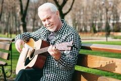 Optimistischer reifer Mann, der Gitarre spielt lizenzfreies stockbild