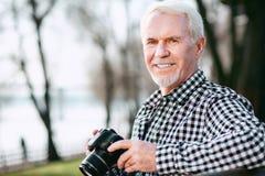 Optimistischer reifer Mann, der mit Fotografie anficht lizenzfreie stockfotografie
