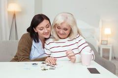 Optimistisches älteren zusammenbauendes Puzzlespiel der Frau und der Pflegekraft stockbilder
