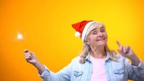 Optimistisk åldrig dam som rymmer bengal ljus som firar Xmas-helgdagsafton, bakgrund arkivfoto