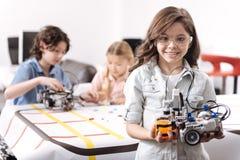 Optimistisk flicka som visar techprojekt på skolan Royaltyfri Bild