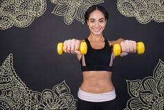 Optimistisk idrottskvinna som ser lycklig medan hållande handvikter Arkivbilder