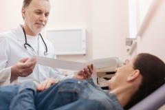 Optimistisk kardiolog som har några goda nyheter för ung dam Arkivfoto