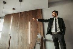 Optimistisk orakad manlig gestikulera arm i korridor arkivfoton