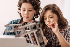 Optimistiska barn som programmerar roboten i vetenskapsstudion arkivfoto