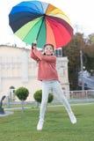 Optimistiskt barn Färgrik tillbehör för gladlynt lynne Parkerar gå för hår för gladlynt barn för flicka långt med paraplyet stay royaltyfria bilder