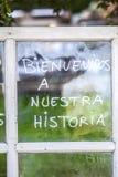 Optimistuttryck som är skriftligt över gamla fönsterexponeringsglas i spanjor royaltyfria foton