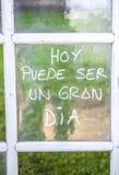Optimistuttryck som är skriftligt över gamla fönsterexponeringsglas i spanjor arkivbild
