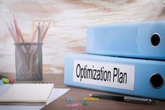 Optimization Plan, Office Binder on Wooden Desk. On the table colored pencils, pen, notebook paper.  Stock Photos