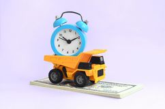 Optimization and rational time management. delegation of work in business. A dump truck loaded with an alarm clock is on a wad of dollar bills. The concept of royalty free stock photo