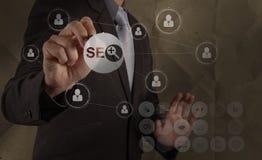 Optimization SEO för motor för affärsmanhanddrawingsearch Arkivbild