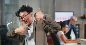 Optinistic Aziatische handelaar die in bureau toejuichen stock videobeelden