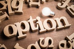 Option Idea. OPTION wood word in scattered wood letters with glowing light bulb royalty free stock photo