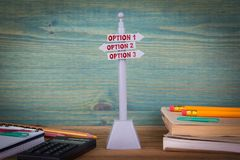 Option 1, option 2, option 3. Signpost on wooden table.  Royalty Free Stock Images