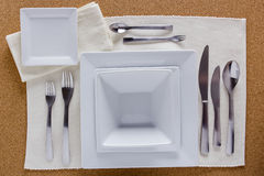 Option table setting with square plates. And a complete set of forks, knives and spoons Stock Photography