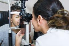 Optisch examen aan de jonge mens, professionele vrouw stock afbeelding