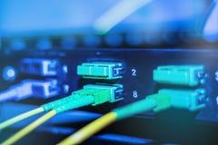 Optische kabel in Internet-netwerkapparaten Groene en gele optische vezelkabel in schakelaar royalty-vrije stock afbeeldingen