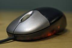 Optische Maus des glatten Silbers und des schwarzen Computers mit rotes Licht glo Stockbild