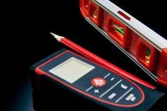 Optisk nivå, laser-avståndsmätare och en blyertspenna som ligger på golvet arkivfoton