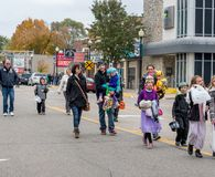 optocht van jonge geitjes en families in Halloween-kostuums, gang in een parade stock fotografie