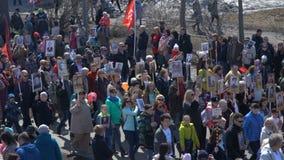 Optocht van mensen met vlaggen en foto's hun verwanten in Onsterfelijk Regiment op jaarlijkse Victory Day May 9