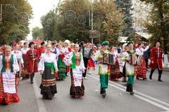 Optocht van studenten van het Instituut van cultuur, dansers in Kozak traditionele kleding, gekleurde rok, groene broeken en kast royalty-vrije stock afbeeldingen