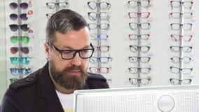 Optométriste mûr travaillant sur un ordinateur à son magasin banque de vidéos