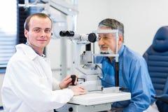 Optometrieconcept - mens die haar onderzochte ogen hebben royalty-vrije stock afbeelding