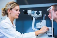 Optometriekonzept - hübscher junger Mann, der seine Augen überprüfen lässt Lizenzfreie Stockfotos