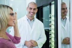 Optometriker, der einen Kunden über Schauspiele und Rahmen konsultiert lizenzfreies stockfoto