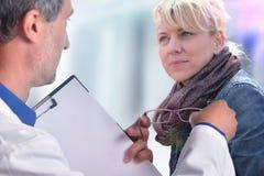 Optometriker, der einer Frau Gläser zeigt lizenzfreie stockfotografie