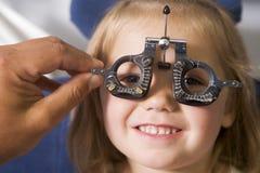 Optometriker im Prüfungraum mit jungem Mädchen Lizenzfreie Stockbilder