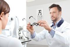 Optometriker med patienten för kvinna för synförmåga för försökram den undersökande I arkivfoton