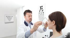 Optometriker med patienten för kvinna för synförmåga för försökram den undersökande I arkivfoto