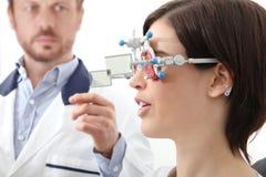 Optometriker med patienten för kvinna för synförmåga för försökram den undersökande I royaltyfri fotografi