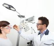 Optometriker med patienten för kvinna för synförmåga för försökram den undersökande I royaltyfria foton