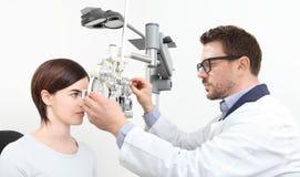 Optometriker som gör synförmåga med tålmodig mätning för kvinna med nolla arkivbild
