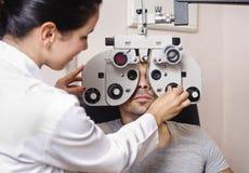 Optometrikerkvinna som ser phoropterkalibrering royaltyfri bild