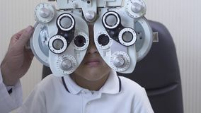Optometrist που εξετάζει τον αρσενικό ασθενή στο phoropter στην κλινική οφθαλμολογίας Αγόρι αφροαμερικάνων που κάνει τη δοκιμή μα απόθεμα βίντεο