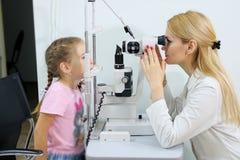 Optometrist рассматривает визирование маленькой девочки на клинике глаза стоковые изображения rf
