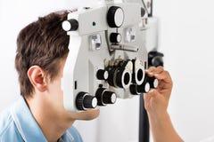 Optometrist регулируя Phoropter для пациента стоковое изображение rf