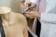 Ιατρικό υπόβαθρο Αίμα άσκησης σπουδαστών περιποίησης που παίρνει το χέρι μανεκέν κάτω από τη επίβλεψη εκπαιδευτικών στοκ φωτογραφίες