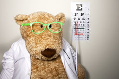 Optometrist. Oversized teddy bear dressed as an optometrist wearing a white lab coat and glasses and pointing to a wall eye chart stock image