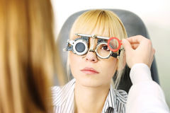 Optometrist. Blond female patient on medical attendance at the optometrist, wearing trial frame for eye testing stock photo