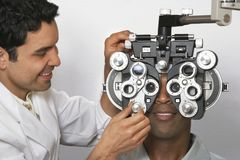 Optometrist Adjusting Panels Of Phoropter While Examining Patient Stock Photography