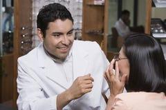 Optometrist assisting patient in choosing glasses Royalty Free Stock Image
