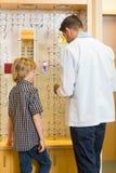 Optometrist And Boy Choosing Eyewear in Opslag stock fotografie