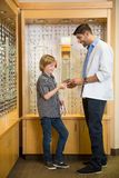 Optometrist And Boy Holding Spectacles In Store Stock Images