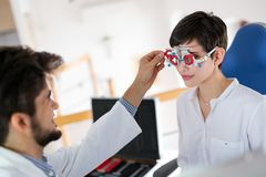 Optometrist checking patient eyesight and vision correction. Optometrist checking patient eyesight and suggesting vision correction treatments Royalty Free Stock Image